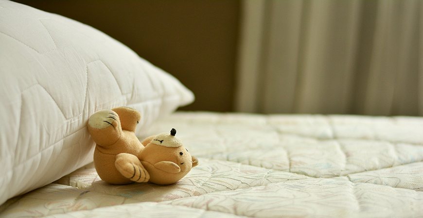 An image depicts a plush toy on top of a mattress.